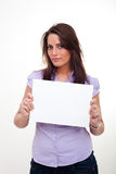 A young woman, holding an empty paper. A young woman, smiling and holding an empty paper in her hands Stock Image