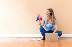 Young woman holding English speaking country flags with laptop. Young woman with English speaking country flags using a laptop computer against a big interior royalty free stock images