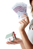 Young woman holding euros bills and house model Royalty Free Stock Images