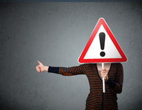 Young woman holding an exclamation road sign Stock Photography