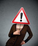 Young woman holding an exclamation road sign Stock Photos