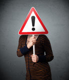 Young woman holding an exclamation road sign Royalty Free Stock Photography