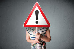 Young woman holding an exclamation road sign Stock Photo