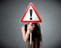 Young woman holding an exclamation road sign Royalty Free Stock Image