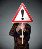 Young woman holding an exclamation road sign Stock Images
