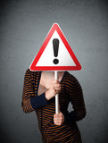 Young woman holding an exclamation road sign Royalty Free Stock Photos