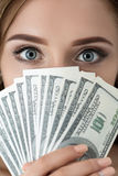 Young woman holding fan of hundred dollar bills Stock Photography