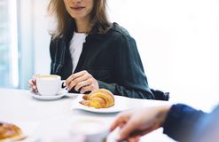 Young woman holding in female hands croissant and drink hot aroma coffee or tea in breakfast time, hipster traveler smile girl royalty free stock image