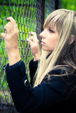Young woman holding on fence Stock Photo