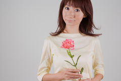 Young woman holding flower. Young Asian woman holding carnation flower Royalty Free Stock Photos