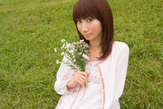 Young woman holding flower. Young Asian woman holding flower bouquet Stock Images