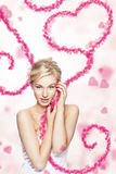 Young woman holding flying heart. Young blond woman holding flying heart made of pink small hearts on light pink background stock photography