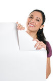 Young woman holding folded corner signboard Royalty Free Stock Photos