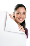 Young woman holding folded corner signboard. Beautiful smiling young woman looking down on a folded corner of a blank signboard to write it on whatever you want royalty free stock photo