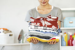 Young woman holding folded laundry. Young woman holding  folded laundry Royalty Free Stock Photo