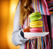 Young woman holding the french pastry macaron in cafe Royalty Free Stock Images