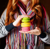 Young woman holding the french pastry macaron in cafe Royalty Free Stock Image