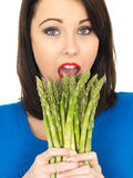 Young Woman Holding a Fresh Asparagus Royalty Free Stock Images