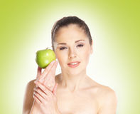 Young woman holding a fresh green apple. On a light green gradient Royalty Free Stock Image