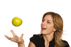 Young woman holding fruit. Young woman playing with green apple over white background Stock Images