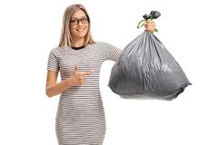 Young woman holding a garbage bag and pointing. Isolated on white background royalty free stock photos