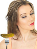Young Woman Holding a Gherkin Royalty Free Stock Photos