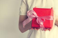 Young woman holding a gift with beautiful ribbon, holiday concep Stock Photography