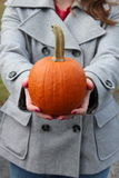 Young woman holding gift of pumpkin Royalty Free Stock Images