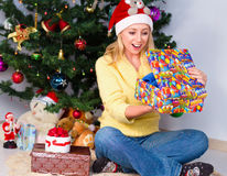 Young woman holding gift and sits near Christmas tree Stock Image