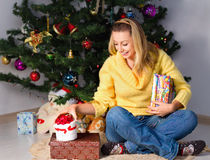 Young woman holding gift and sits near Christmas tree Royalty Free Stock Images