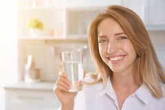 Young woman holding glass with clean water