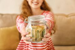 Young woman holding glass jar with dollars indoors. Money savings concept royalty free stock photo