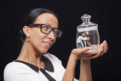 Young woman holding a glass jar, in which sits a little girl Stock Images