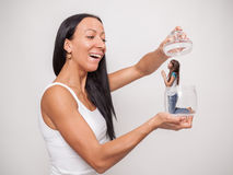 Young woman holding a glass jar, in which sits a little girl Royalty Free Stock Photos