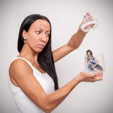 Young woman holding a glass jar, in which sits a little girl Stock Photography