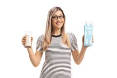 Young woman holding a glass of milk and a milk carton. Isolated on white background Royalty Free Stock Images