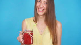 Young woman holding a glass of red smoothies stock footage