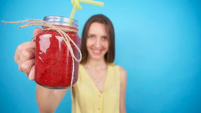 Young woman holding a glass of red smoothies stock video footage