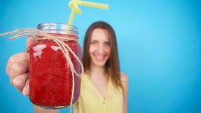 Young woman holding a glass of red smoothies stock video