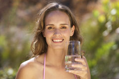 Young woman holding a glass of water, close-up Stock Photo
