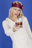 Young Woman Holding a Glass of Whiskey Saying Cheers Wearing Red Party Hat. Attractive Young Woman Holding a Glass of Whiskey Saying Cheers Wearing Red Party Hat Stock Photo