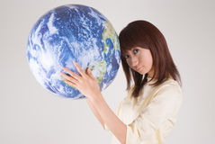 Young woman holding globe. Looking at camera Royalty Free Stock Image