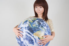 Young woman holding globe. Young woman looking at camera with globe in hands Royalty Free Stock Photography