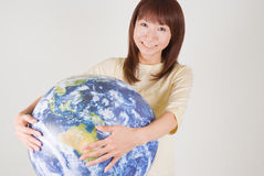 Young woman holding globe. Young woman smiling with globe in hands Royalty Free Stock Images