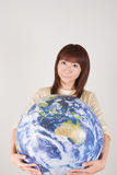Young woman holding globe. Young woman looking at camera with globe in hands Stock Photography