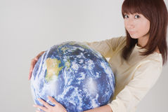 Young woman holding globe. Side view of young Asian woman holding globe Royalty Free Stock Image