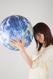 Young woman holding globe. With eyes closed Royalty Free Stock Photos
