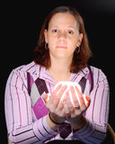 Young Woman, holding a glowing object. A young woman holding a glowing object on a black background stock photography