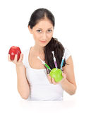 Young woman holding GMO apple with syringe. Young attractive woman holding GMO apple with three syringe on white Stock Photo