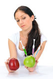 Young woman holding GMO apple with three syringe. Young attractive woman holding GMO apple with three syringe on white Royalty Free Stock Photos